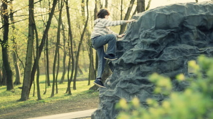 Young boy climbing a rock in the park, pan shot