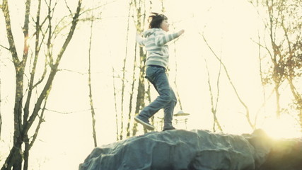 Young boy climb to the top of a rock and raise his hands