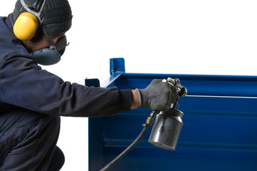Industrial painter painting metal product with spray gun.
