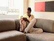 African American woman reading a book on the couch