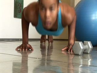 Young African American woman exercising and doing pushups