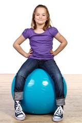 kleines mädchen sitzt auf einem gymnastikball