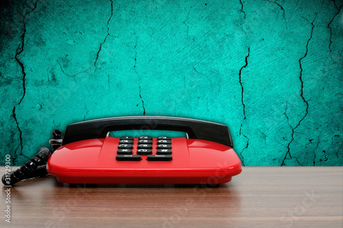 red phone on dirty blue wall background