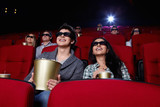 Funny people are watching a movie in 3D glasses in cinema