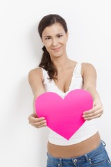 Lovesick woman smiling happily with paper heart