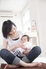 母親のあぐらの上に座る赤ちゃん