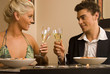 Young couple eating a meal and toasting at a restaurant