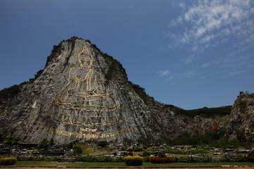 Engraving Sukhothai-style Buddha image on mountain surface