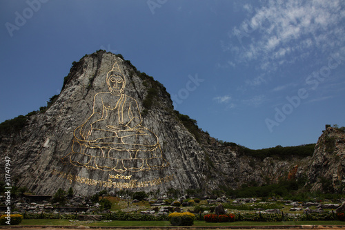 Engraving Sukhothai-style Buddha image on mountain surface