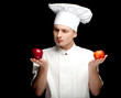 male cook in white uniform with apples, black background