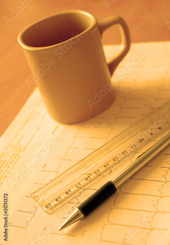 mug, pen and a ruler on the electrocardiogram