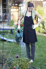 Frau giesst im Garten