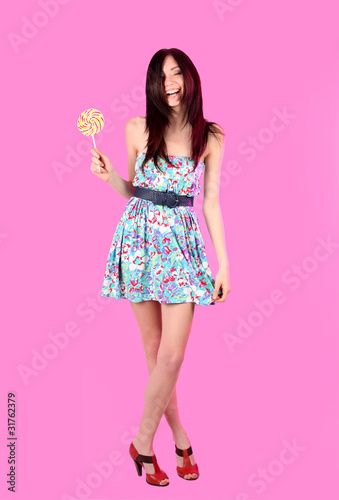 Glamorous girl wearing colorful dress with lollipop
