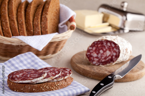 Served kitchen table, sandwich on napkin, salami, breadbasket, s