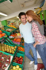Couple at the supermarket doing grocery shopping