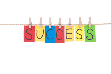 Success, words hang by wooden peg