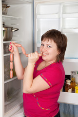 Happy woman taking sausages from fridge