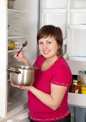 woman with pan near refrigerator