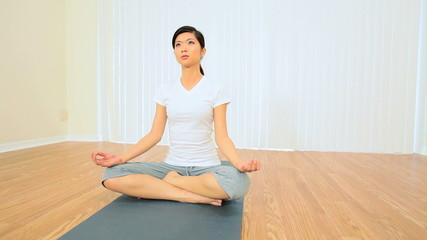 Asian Girl Practicing Yoga in Fitness Studio