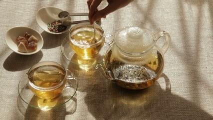 Woman mixes brown sugar in cup of tea