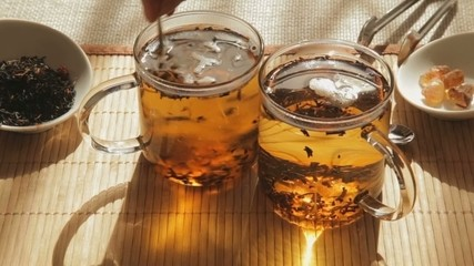 Woman mixes brown sugar in glass of tea