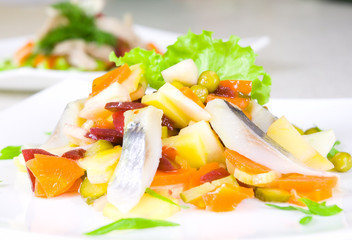 salad of beetroot, carrot, potato, green leek and herring
