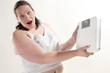Übergewichtige erwachsene Frau hält eine Waage