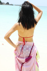 Vacation, A girl push hair in bikini and a pink shawl.