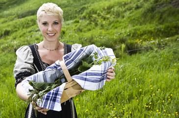 Junge Frau in ländlicher Tracht sammelt Wildkräuter