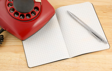 Blank notebook, pen and telephone on the wooden table