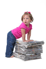 Toddler leaning against stacks of newspapers