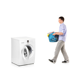 Man with a laundry basket going towards a washing machine