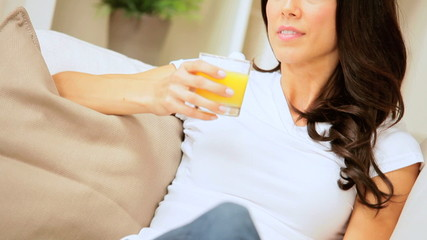 Female on Home Couch Drinking Orange Juice