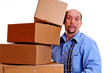 Man carrying heavy boxes with one about to fall.