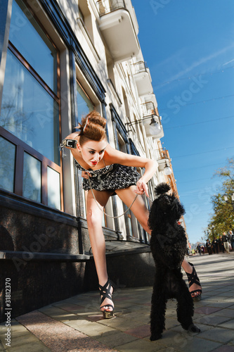 A girl with a dog standing on the street