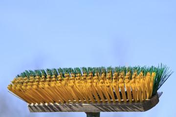 Besen mit grünen und gelben Borsten
