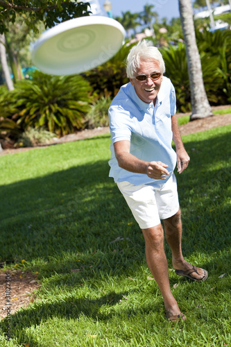 Happy Senior Man Throwing Frisbee Outside in Sunshine