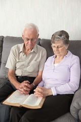 An Elderly Couple Having Worship With The Bible