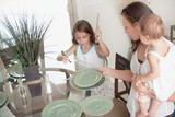 A Mother And Daughter Setting The Table Together