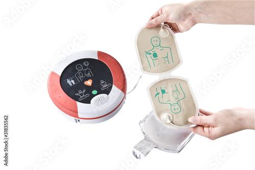 Leinwanddruck Bild AED Elektroden entnehmen