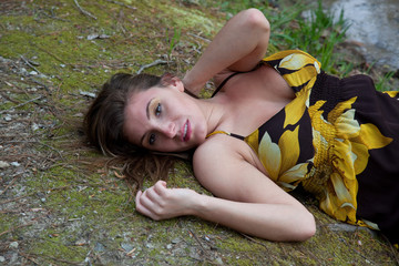 Pretty woman reclining in the woods with eye contact