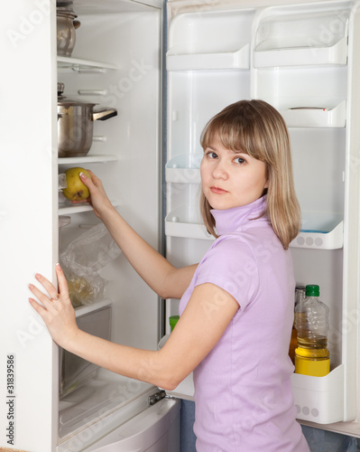 woman taking  apple  from refrigerator