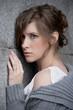 Обиженная девушка на фоне серой каменной стены