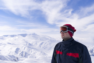 Young skier is looking on the mountain landscape