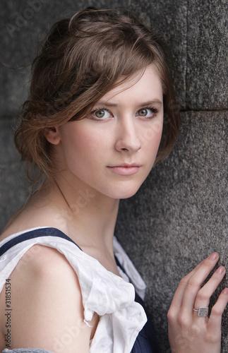 Расстроенная девушка на фоне серой каменной стены