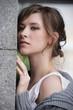 Девушка на фоне серой каменной стены