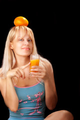 Studio portrait of young beautiful woman drinking orange juce