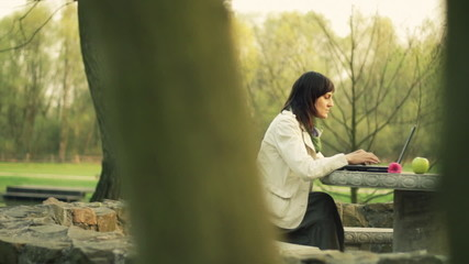 Woman with laptop, receiving phone call in the park, dolly shot