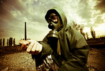 Scientist with gas mask examining rock