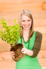 Portrait happy woman hold plant spring gardening